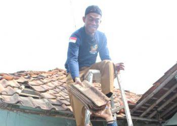 Bupati Subang H Ruhimat saat ikut menurunkan genting rumah warga yang akan direnovasi (Foto: deny Suhendar)