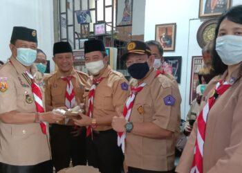 Ketua Kwarcab Gerakan Pramuka KBB Aseng Junaedi, memberikan potongan tumpeng pada Ketua Mabi Pariwisata, Heri Partomo, usai pelantikan Saka Pariwisata, Selasa (16/2/2021). (Foto : Heny/dara.co.id)
