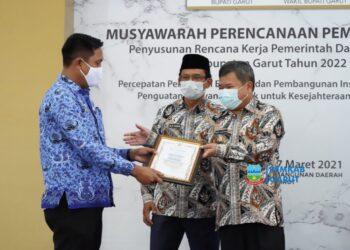Camat Pasirwangi, Saepul Hidayat, mendapatkan penghargaan dari Bupati Garut, Rudy Gunawan, dalam pelaksanaan Musrenbang Tingkat Kabupaten Garut (Foto: Istimewa)